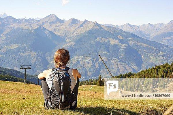 Rückansicht einer Wanderin  die über die Berglandschaft blickt  Aostatal  Aosta  Italien