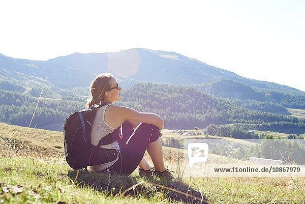 Wanderin sitzt mit Blick auf die Berglandschaft  Aostatal  Aosta  Italien