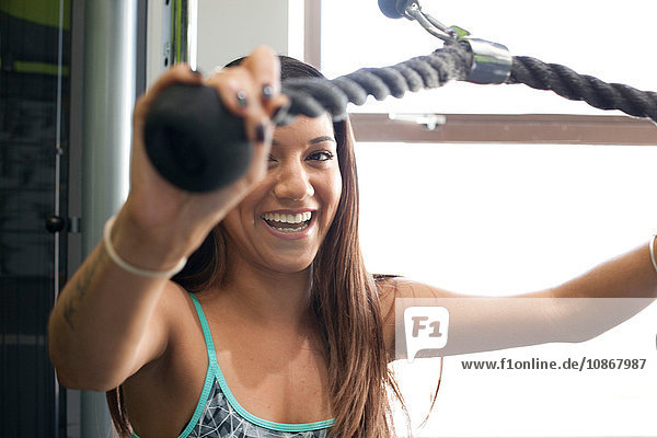Woman in gym using exercise machine looking at camera smiling