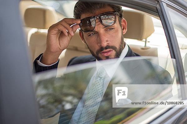 Junger Geschäftsmann hält Sonnenbrille auf dem Rücksitz eines Autos hoch  Dubai  Vereinigte Arabische Emirate