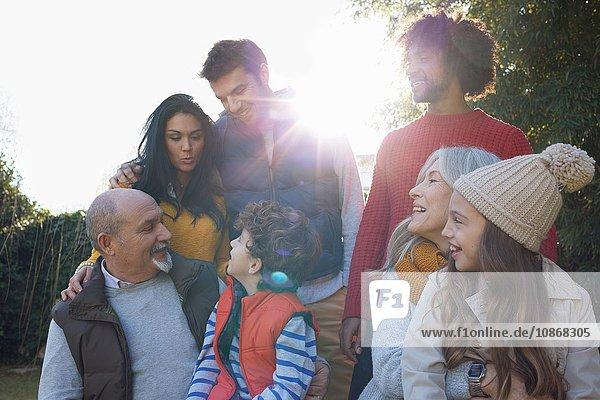 Mehrgenerationen-Familie kauert sich zusammen und plaudert und lächelt