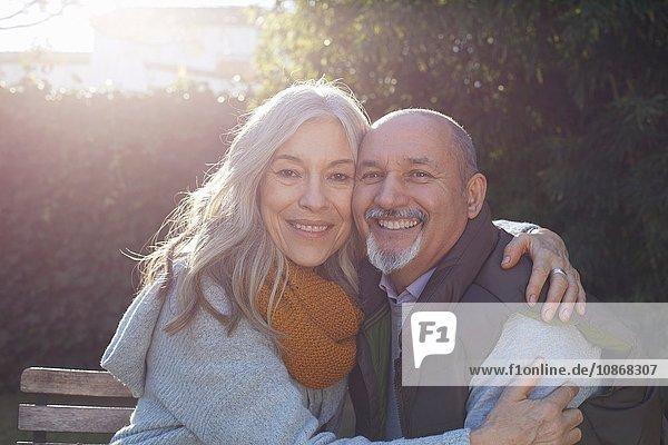 Mature couple hugging  looking at camera smiling