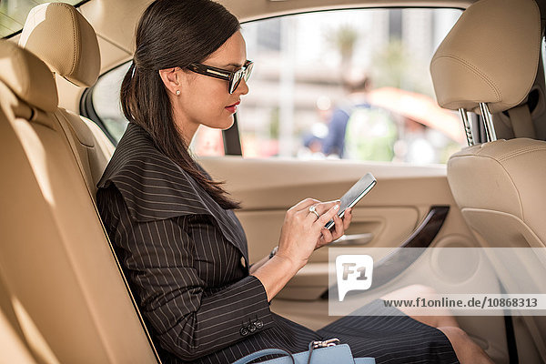 Businesswoman using smartphone touchscreen in car backseat  Dubai  United Arab Emirates