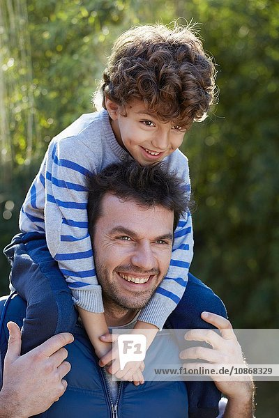 Father carrying smiling son on shoulders