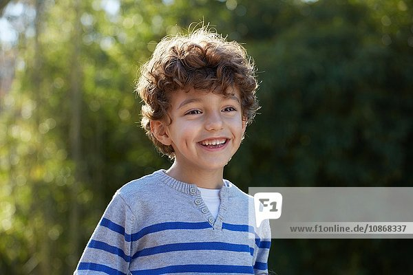 Portrait of curly haired boy looking away smiling
