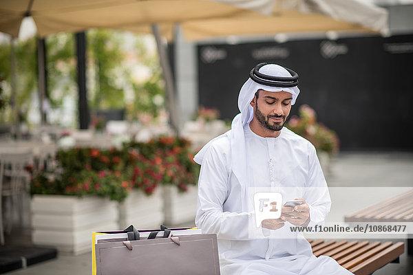 Männlicher Einkäufer in traditioneller Kleidung aus dem Nahen Osten sitzt auf Bank und liest Smartphone-Text  Dubai  Vereinigte Arabische Emirate