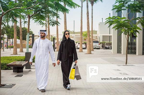 Einkaufspaar aus dem Nahen Osten in traditioneller Kleidung auf der Straße  Dubai  Vereinigte Arabische Emirate