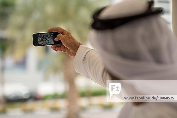 Über die Schulter eines Mannes aus dem Nahen Osten  der mit Freunden in einem Cafe ein Smartphone mitnimmt  Dubai  Vereinigte Arabische Emirate