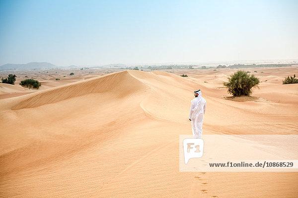 Rückansicht eines jungen Mannes aus dem Nahen Osten in traditioneller Kleidung  der in der Wüste spazieren geht  Dubai  Vereinigte Arabische Emirate