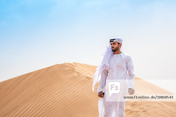 Mann aus dem Nahen Osten trägt traditionelle Kleidung auf Wüstendüne  Dubai  Vereinigte Arabische Emirate
