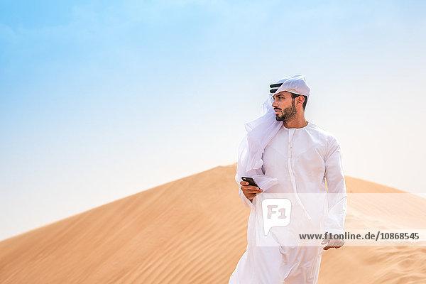 Mann aus dem Nahen Osten trägt traditionelle Kleidung mit Smartphone auf Wüstendüne  Dubai  Vereinigte Arabische Emirate