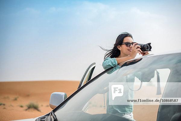 Weibliche Touristin fotografiert vom Geländewagen aus in der Wüste  Dubai  Vereinigte Arabische Emirate