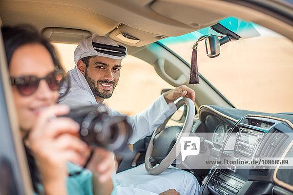 Weibliche Touristin im Geländewagen in der Wüste beim Fotografieren  Dubai  Vereinigte Arabische Emirate