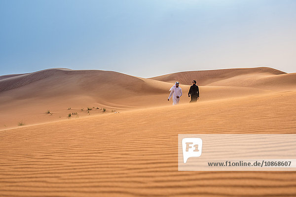Distant view of couple wearing traditional middle eastern clothes walking on desert dune  Dubai  United Arab Emirates