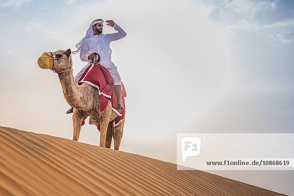 Mann in traditioneller nahöstlicher Kleidung auf Kamel in der Wüste  Dubai  Vereinigte Arabische Emirate