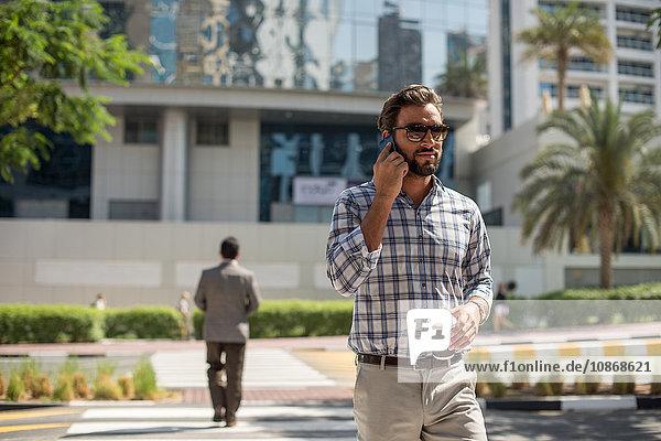 Junger Mann auf Fußgängerüberweg im Gespräch auf Smartphone  Dubai  Vereinigte Arabische Emirate