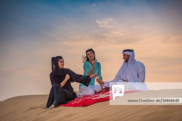 Einheimisches Paar in traditioneller Kleidung picknickt mit Touristin auf Wüstendüne  Dubai  Vereinigte Arabische Emirate