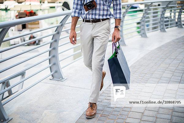 Taille eines jungen Mannes  der mit einer Einkaufstasche am Wasser spazieren geht  Dubai  Vereinigte Arabische Emirate