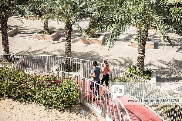 High angle view of running couple running down footbridge  Dubai  United Arab Emirates