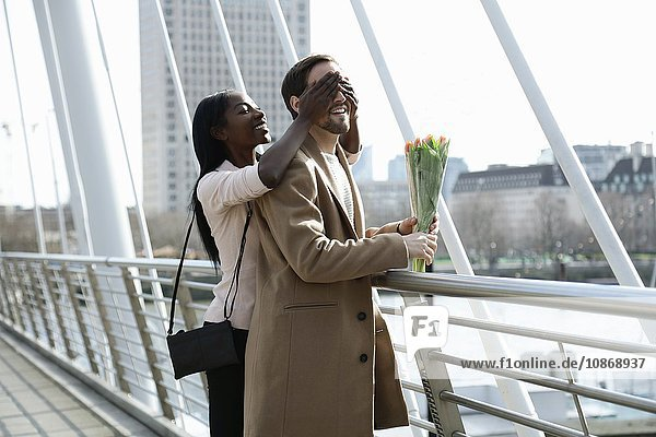 Mann steht auf der Brücke  hält Blumen in der Hand  Frau überrascht ihn  verdeckt von hinten seine Augen