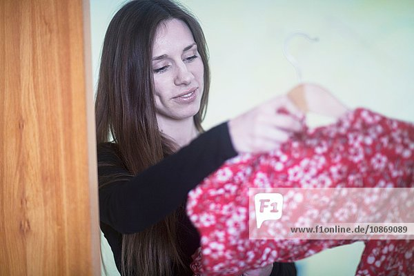 Junge Frau zu Hause  die entscheidet  was sie anziehen will