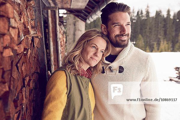 Paar  das im Winter vor einem Blockhaus steht  Elmau  Bayern  Deutschland