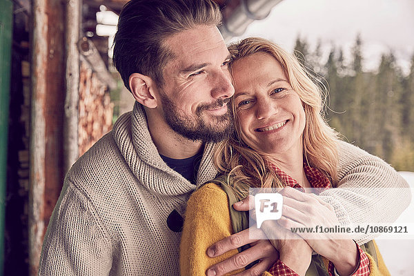 Portrait of romantic couple standing outside log cabin in winter  Elmau  Bavaria  Germany