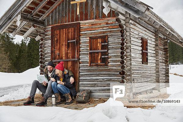 Couple reading map sitting outside log cabin in winter  Elmau  Bavaria  Germany