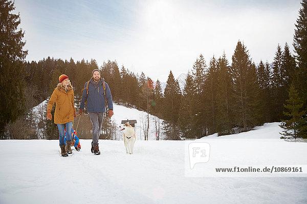 Eltern ziehen Söhne auf dem Schlitten in verschneiter Landschaft  Elmau  Bayern  Deutschland