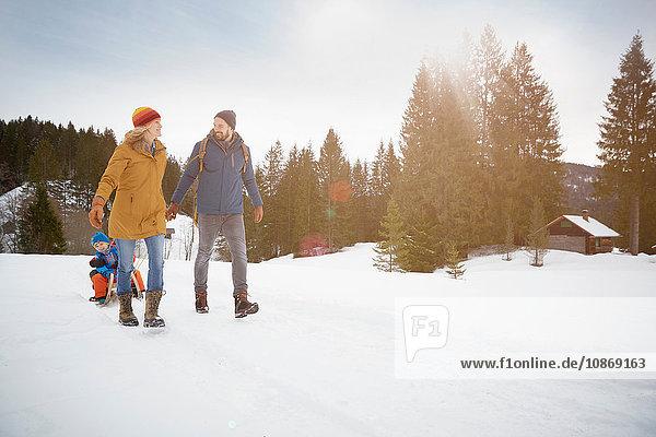 Parents pulling sons on toboggan in snow landscape  Elmau  Bavaria  Germany