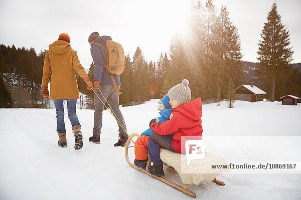 Rear view of parents pulling sons on toboggan in snow landscape  Elmau  Bavaria  Germany