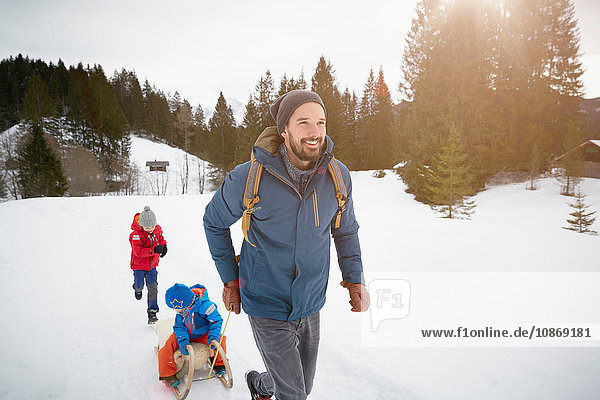 Young man pulling sons on toboggan in snow covered landscape  Elmau  Bavaria  Germany