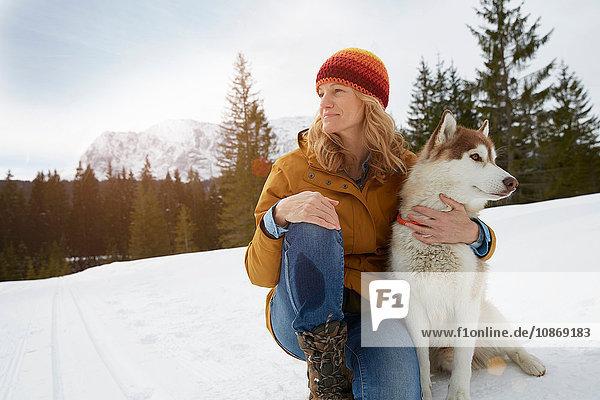 Frau sitzt mit Husky in schneebedeckter Landschaft  Elmau  Bayern  Deutschland