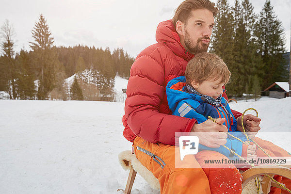 Young man and son tobogganing in snow  Elmau  Bavaria  Germany