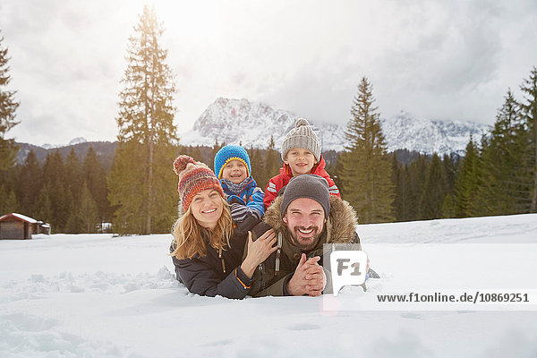 Portrait of parents and sons lying in snow covered landscape  Elmau  Bavaria  Germany
