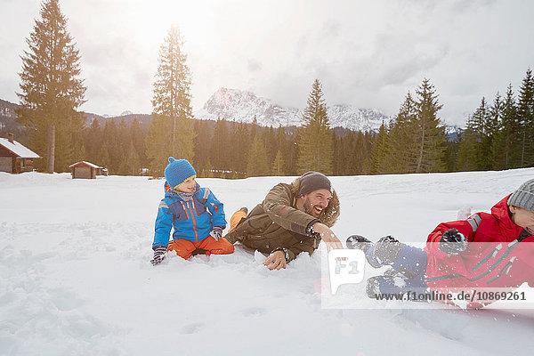 Junger Mann und Söhne bei Schneeballschlacht im Winter  Elmau  Bayern  Deutschland
