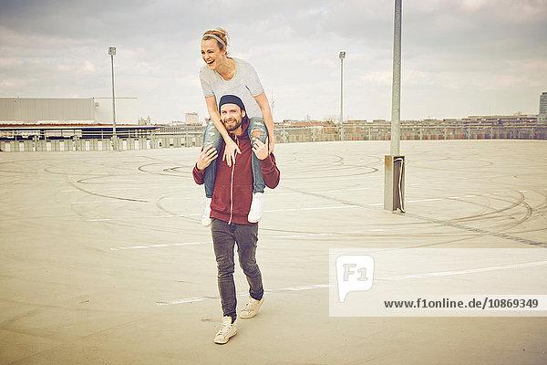 Mittelgroßer Erwachsener  der seine Freundin auf dem Parkplatz auf dem Dach über die Schulter nimmt