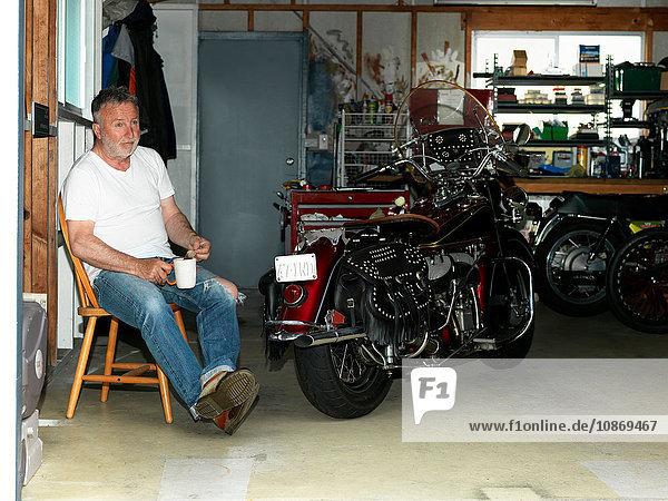 Älterer Mann sitzt mit einem Kaffee in der Garage mit Motorrad