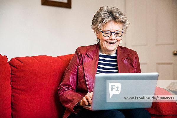 Ältere Frau auf Wohnzimmer-Sofa beim Tippen am Laptop