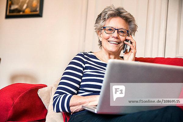 Ältere Frau auf Wohnzimmer-Sofa  die sich mit einem Smartphone unter Verwendung eines Laptops unterhält