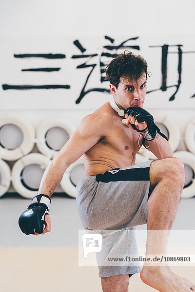 Man in gym wearing boxing gloves in kickboxing stance looking at camera