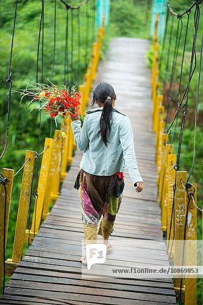 Young woman on footbridge with flowers  Shan State  Keng Tung  Burma