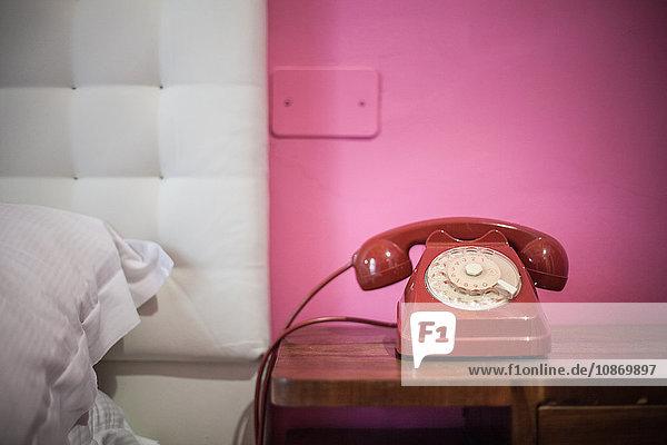 Rotes Drehtelefon auf dem Nachttisch