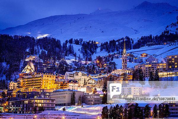 Dorf unter dem Berg auf schneebedeckter  abends beleuchteter Landschaft  Sankt Moritz  Schweiz
