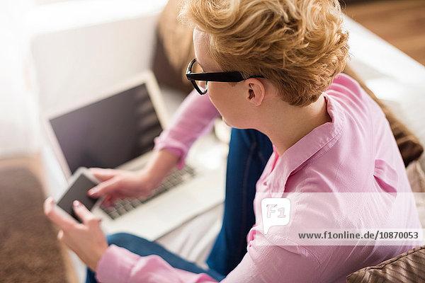 Frau schreibt auf Smartphone auf dem Sofa