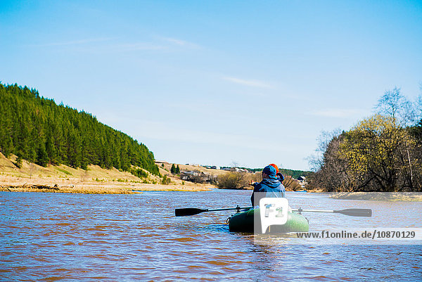 Rear view of couple rowing on river in dinghy
