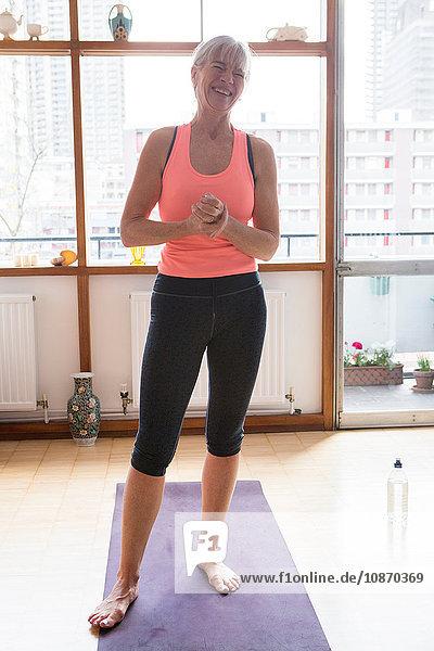 Glückliche Frau auf Yogamatte zu Hause