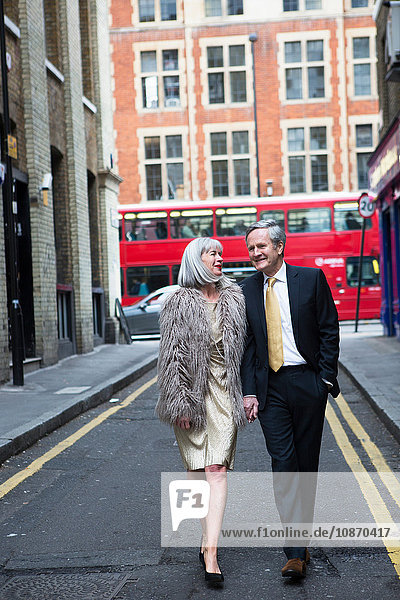 Couple dressed up and out walking on street