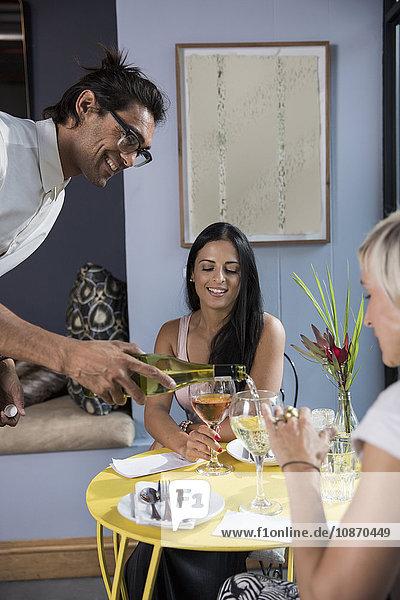 Kellner schenkt Wein für Kunden im Restaurant ein