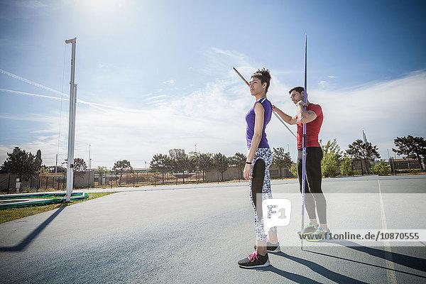Mann instruiert Speerwerferin auf Sportplatz